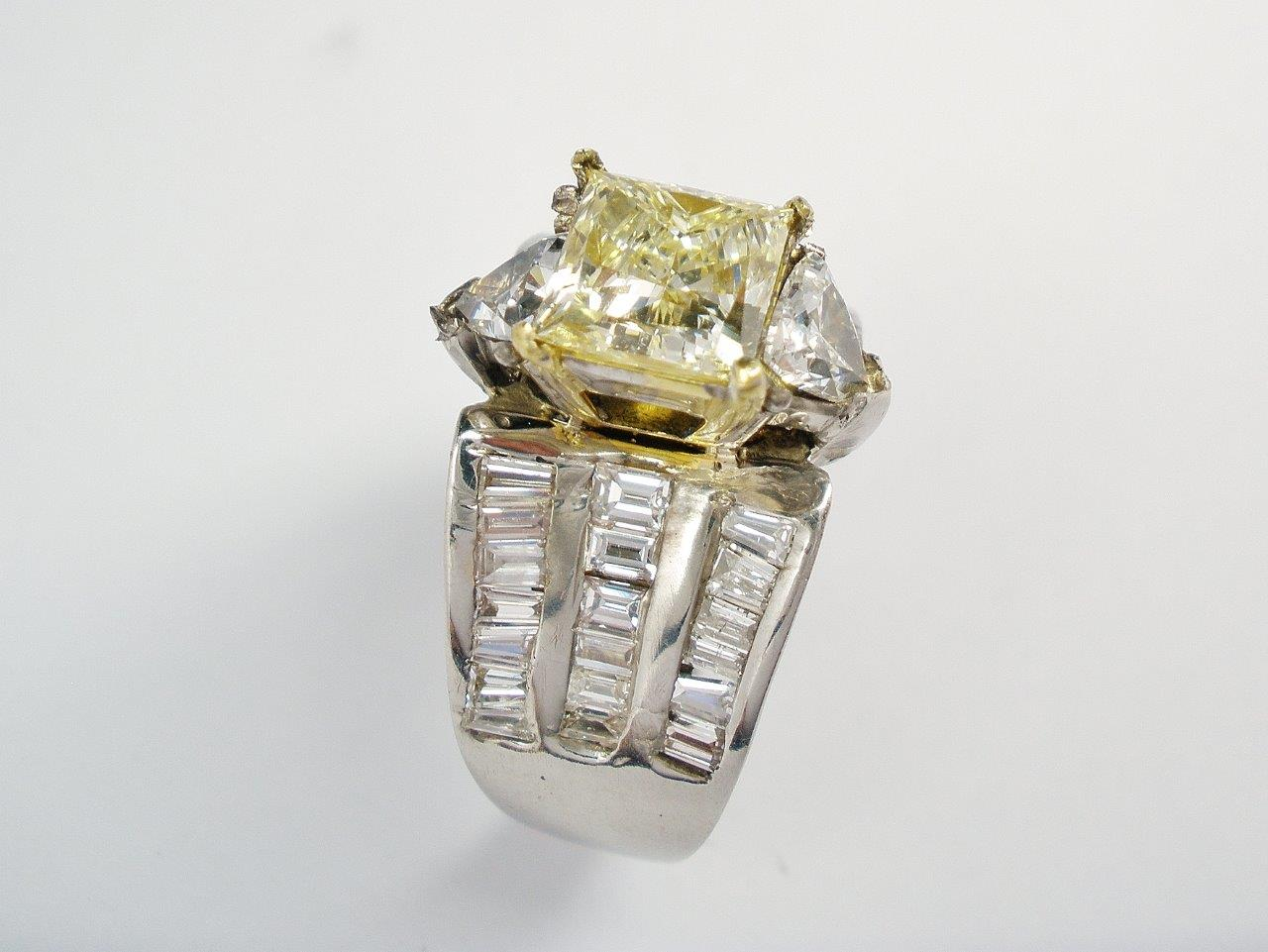 A 2ct. champagne coloured princess cut diamond with a white trilliant cut diamond set above and below and a broad 18ct. white gold shank channel set with 3 rows of baguette diamonds.