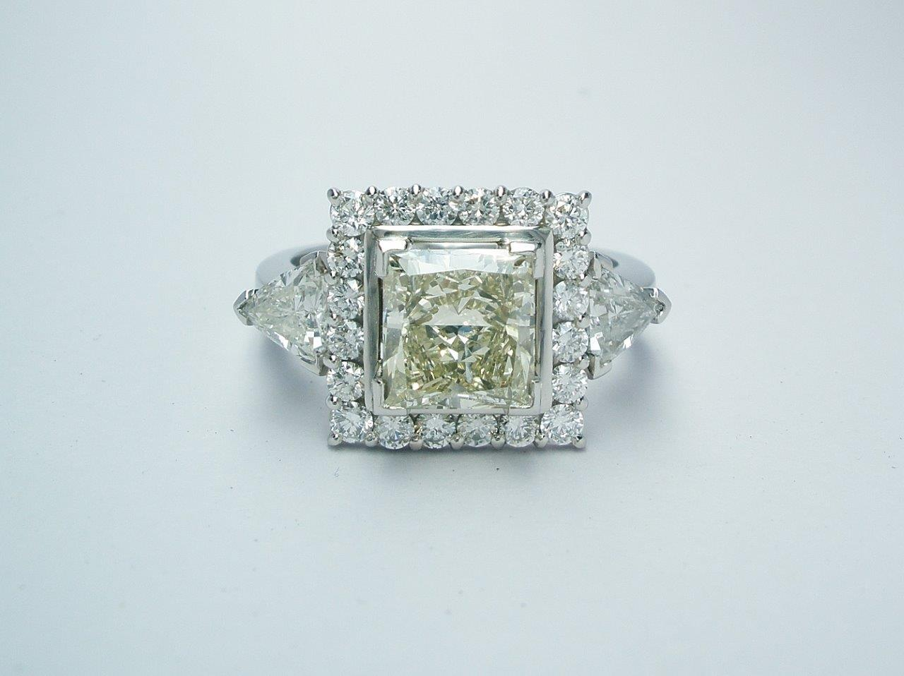 The 2ct. champagne princess cut diamond mounted centrally in a part channel set white round brilliant cut square 'Halo' cluster platinum ring with the white trilliant diamonds set on the outside shoulders.