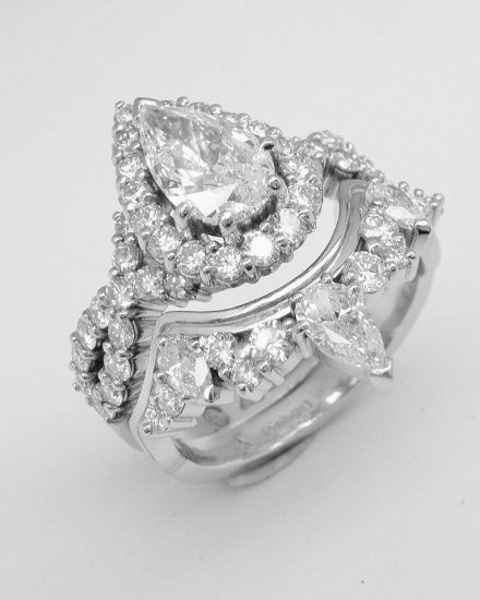A pear and brilliant cut diamond wedding ring shaped to fit around a pear shaped 'halo' cluster engagement ring with criss-cross diamond shoulders.