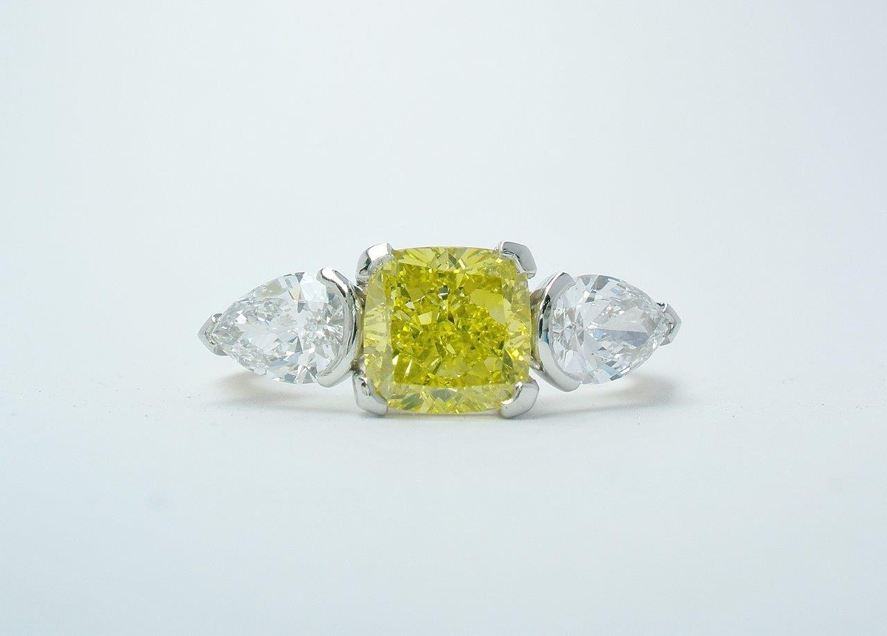 A 1.50ct. Canary yellow, square cushion cut diamond and 'D' coloured white pear shaped diamonds mounted as a 3 stone ring in 18ct. yellow gold and platinum.