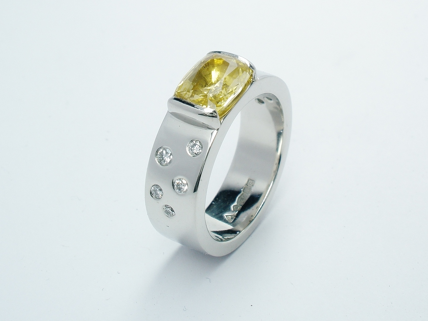 A rectangular cushion cut yellow sapphire and flush set round brilliant cut diamonds mounted in platinum.