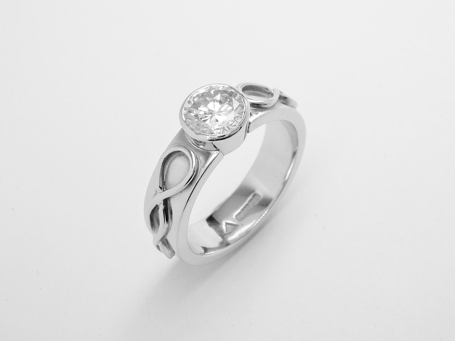 Single rub-over set round brilliant cut diamond ring mounted in platinum with Celtic motif overlay on shoulders.