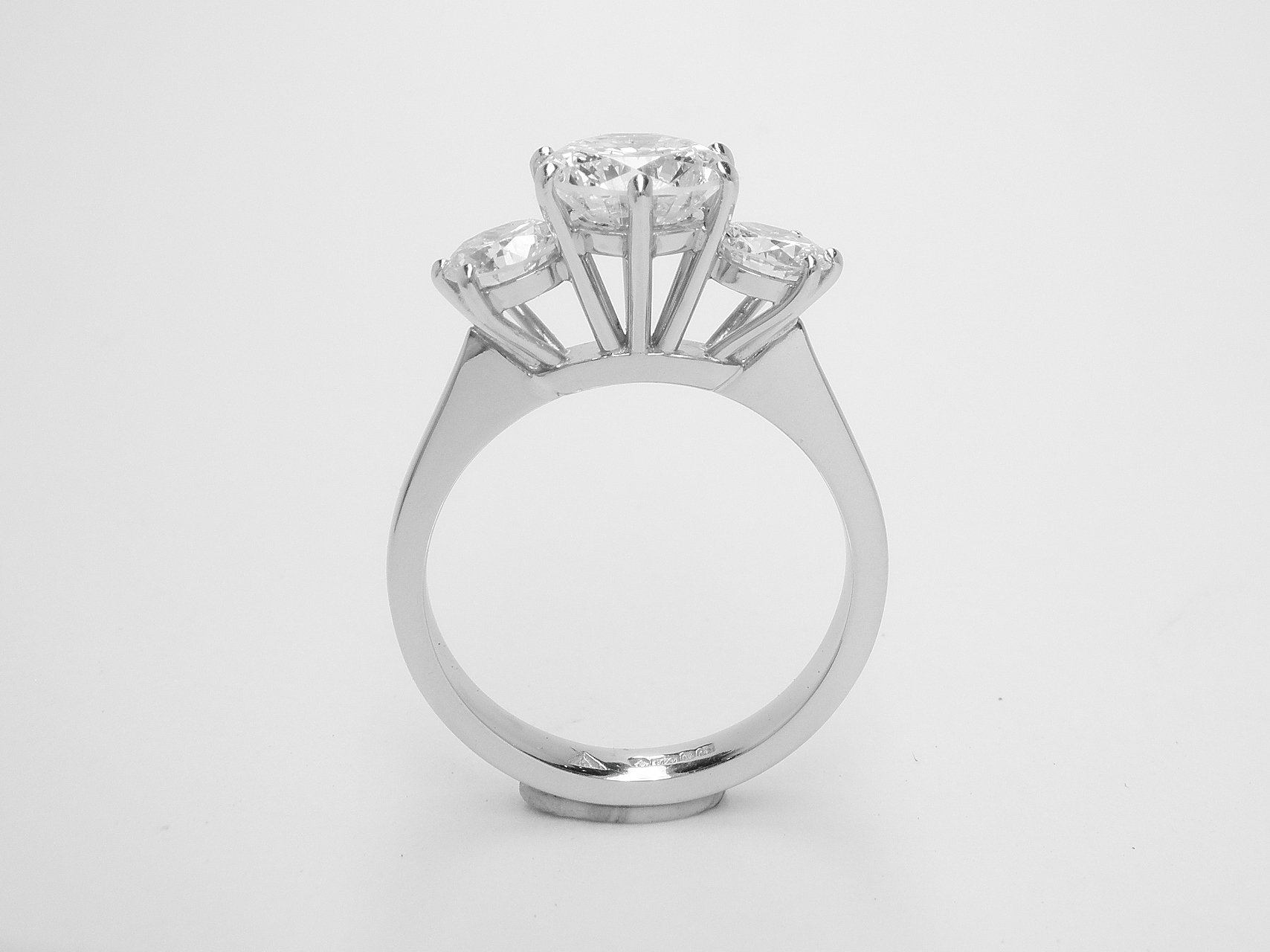 A 3 stone round brilliant cut diamond ring mounted in platinum with large raised centre diamond.