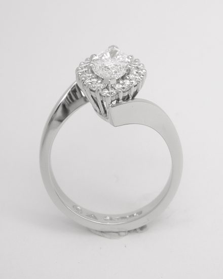 A marquise diamond and round brilliant cut diamond cross-over style ring mounted in platinum.