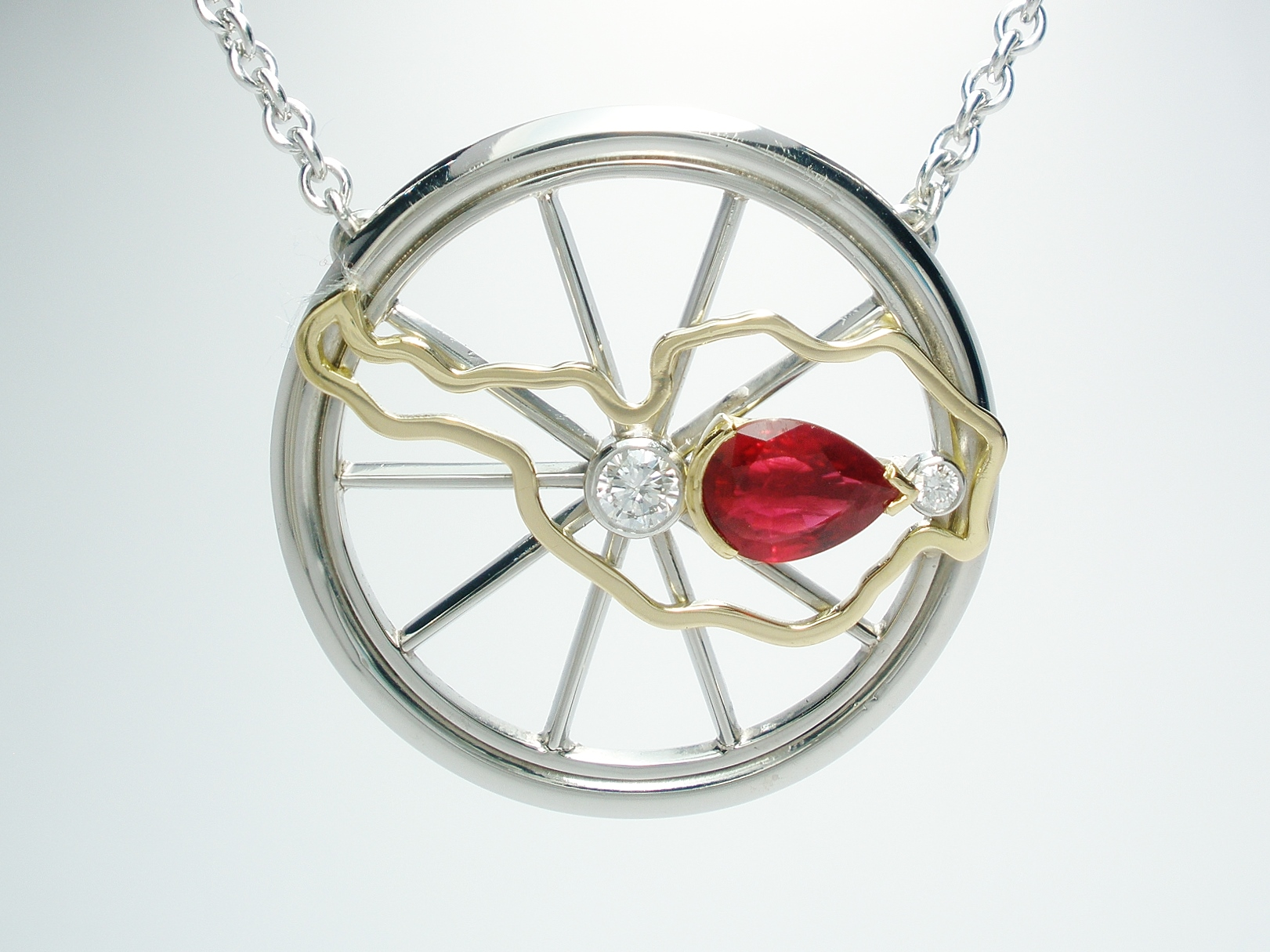 A pear shaped ruby and round brilliant cut 3 stone palladium mountain bike wheel style pendant with 18ct. yellow gold Austrian map overlay.