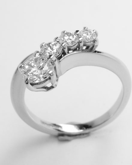 A 4 stone round brilliant cut diamond 'comet' engagement ring mounted in platinum.