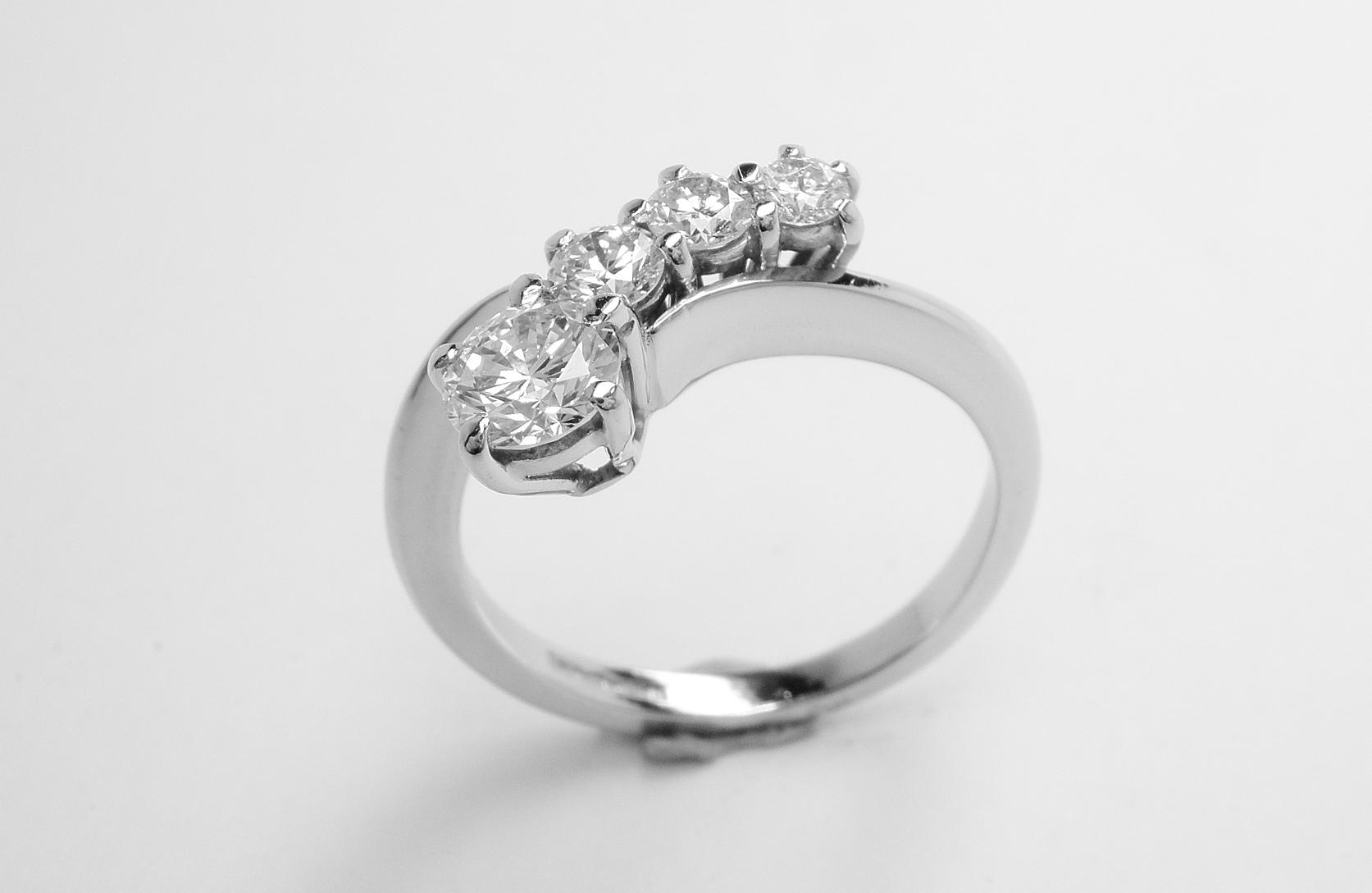 A 4 stone round brilliant cut diamond 'comet' engagement ring mounted in platinum.
