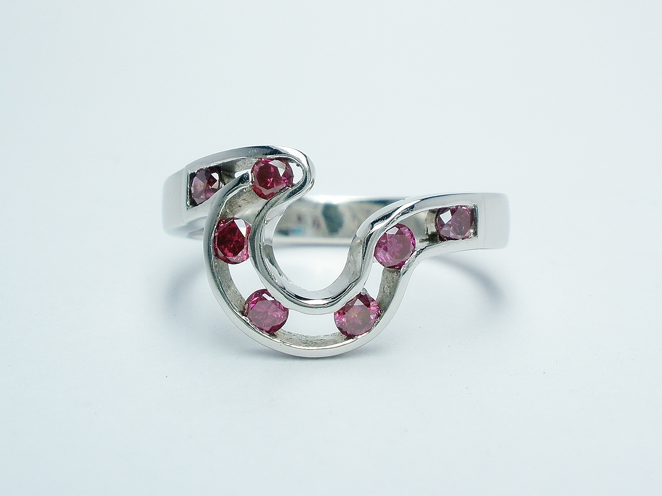 A pink diamond 7 stone open channel set shaped wedding ring shaped to fit around 4 stone comet engagement ring.