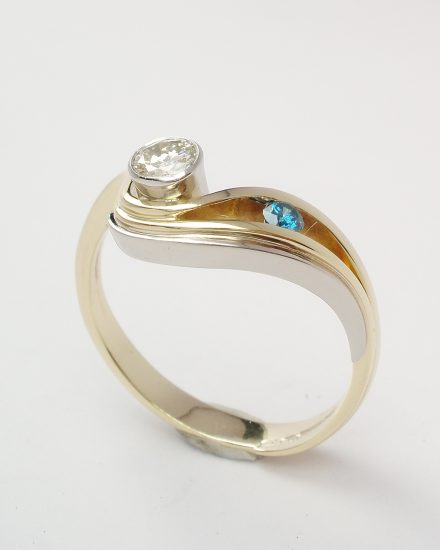 An ocean blue and white 2 stone round brilliant cut diamond 'wave' style ring mounted in 18ct. yellow gold and platinum.