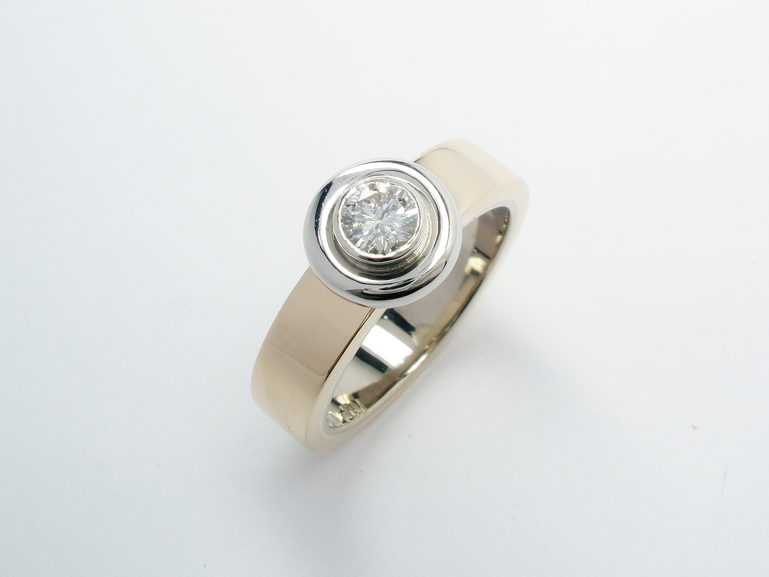 A single stone round brilliant cut diamond 'Doughnut' style ring mounted in 9ct. yellow gold and platinum.