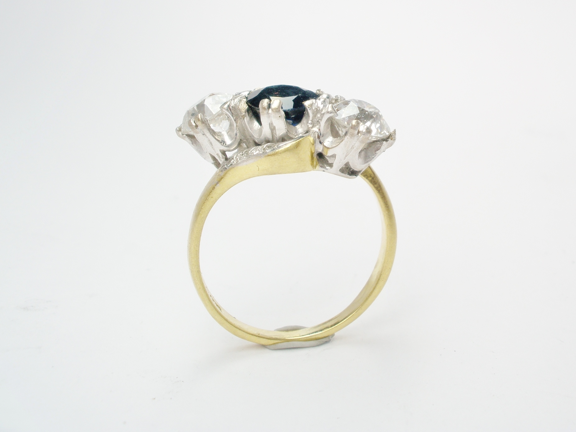 A 3 stone cross-over diamond and sapphire ring mounted in an 18ct. white gold block style setting with an 18ct. yellow shank set with small diamond set in the shoulders.