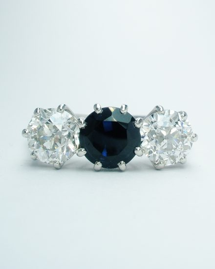3 stone sapphire & diamond peg set ring mounted in platinum with small diamond channel set in the shoulders.