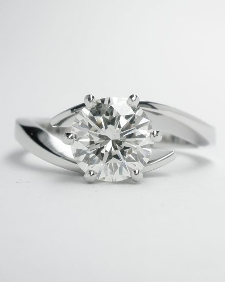 1.02ct. round brilliant cut diamond single stone open cross-over style ring mounted in platinum.