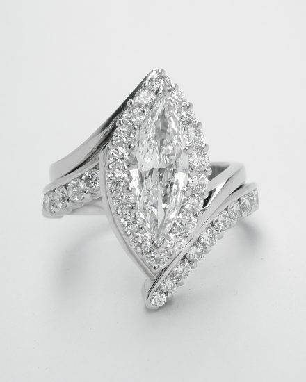 A platinum 15 stone part channel set wedding ring shaped to fit around a marquise shaped diamond cluster cross-over engagement ring.