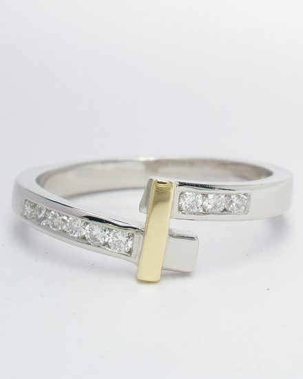 A palladium wedding ring shaped to fit a single stone cross-over diamond ring channel set with diamonds and an 18ct. yellow gold bridge.