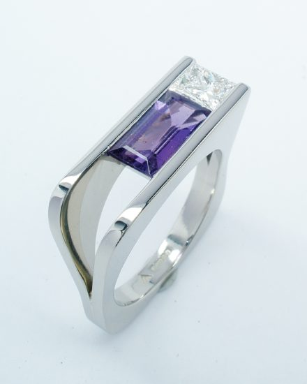 A purple baguette sapphire and princess cut diamond plateau topped square ring mounted in palladium.