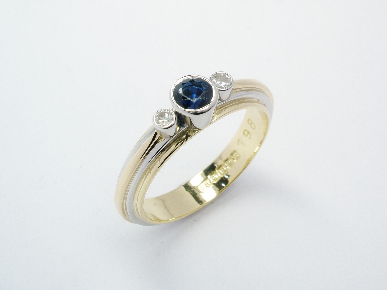Using the wedding ring as the main ring applied a narrower platinum band over this, rub-over set the diamonds and sapphire & applied.