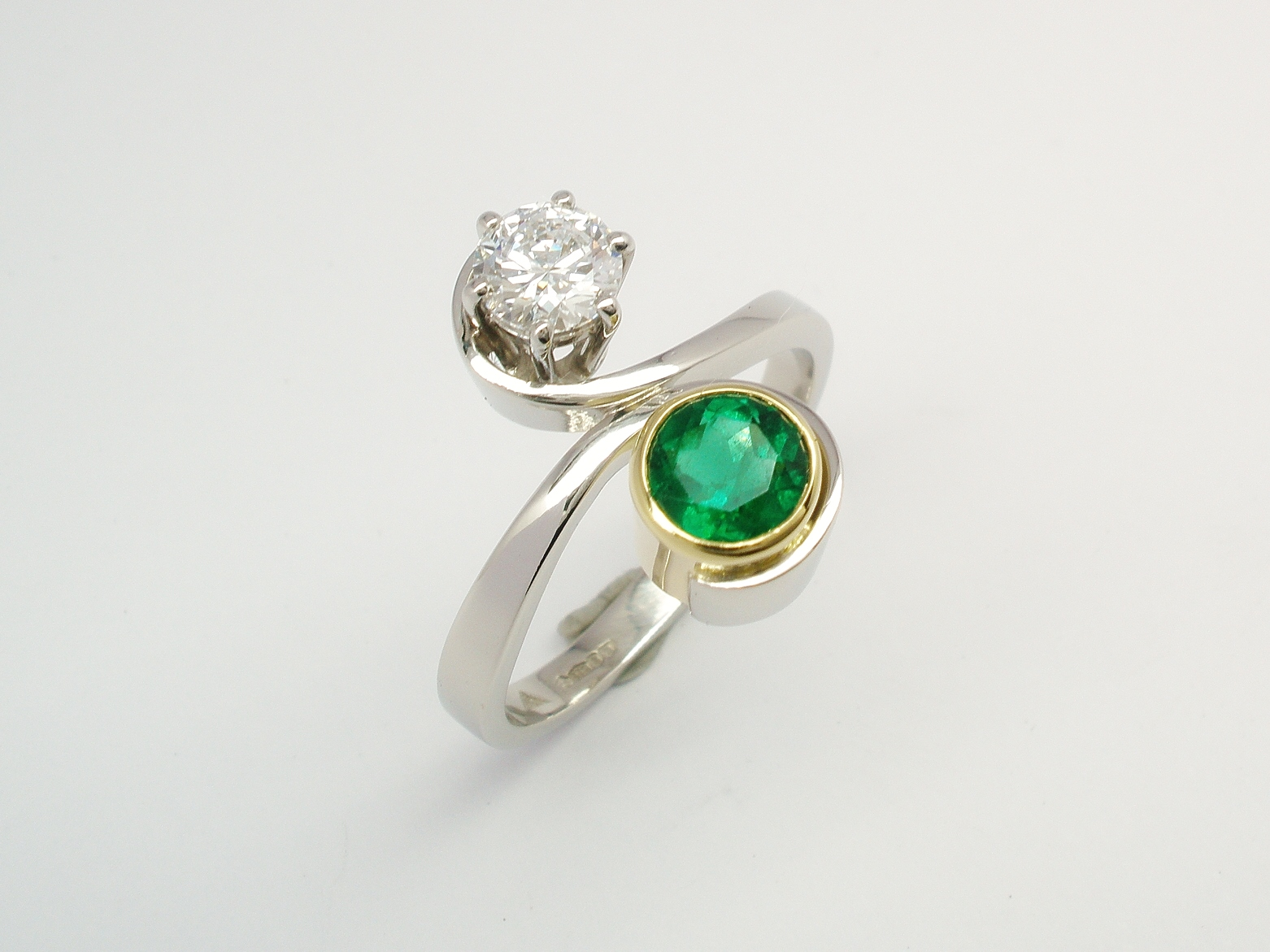 0.50ct 'D' Internally Flawless Diamond and round emerald 2 stone ring in the form of an initial 'S' mounted in platinum & 18ct yellow gold.