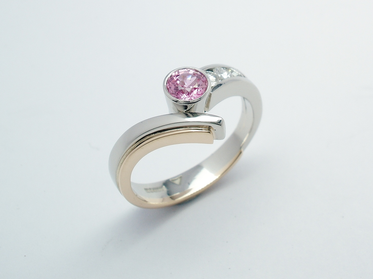 A round pink sapphire and diamond 4 stone ring mounted in palladium, platinum & 9ct red gold.