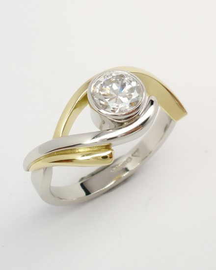 A single stone rub-over set round brilliant cut diamond 'open cross-over' ring mounted in platinum and 18ct yellow gold.