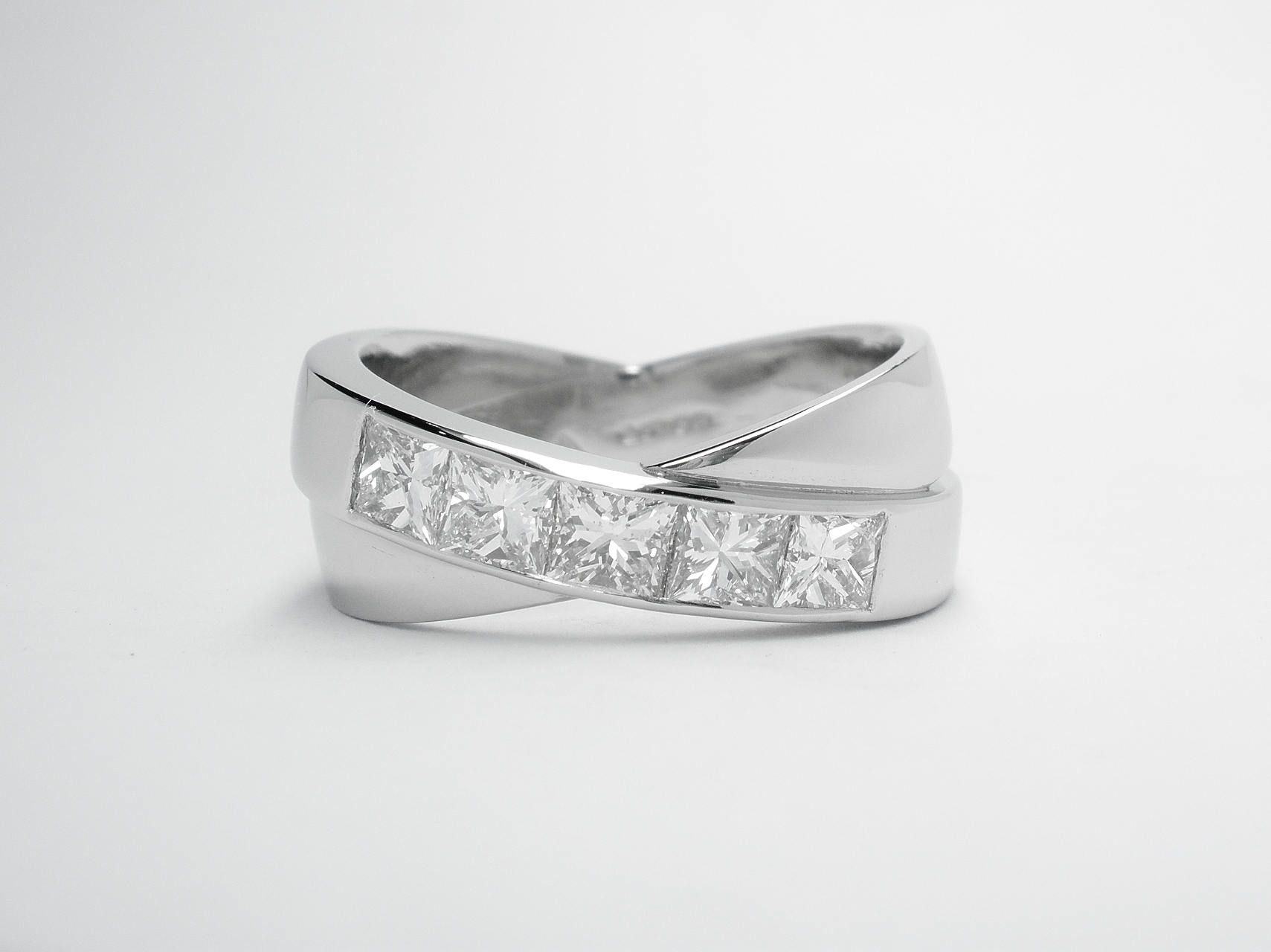 A 5 stone channel set princess cut diamond 'X' style ring mounted in platinum.