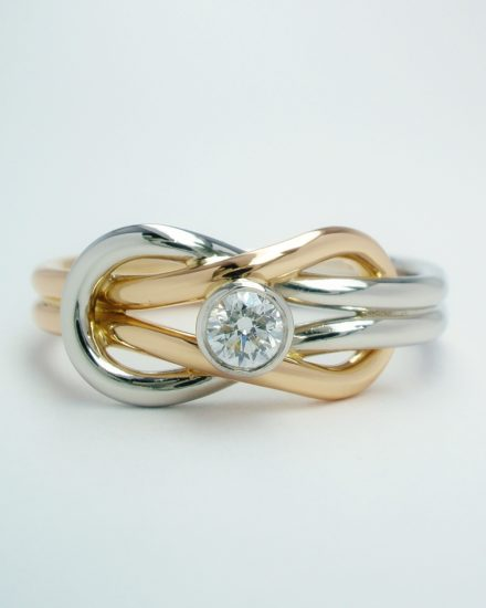 A rub-over set single stone round brilliant cut diamond 'Reef knot' style ring mounted in platinum & 18ct. red gold.