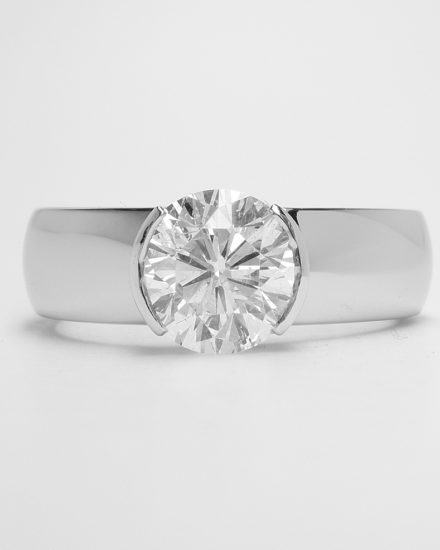 A part rub-over set single stone round brilliant cut diamond ring mounted in palladium and platinum.