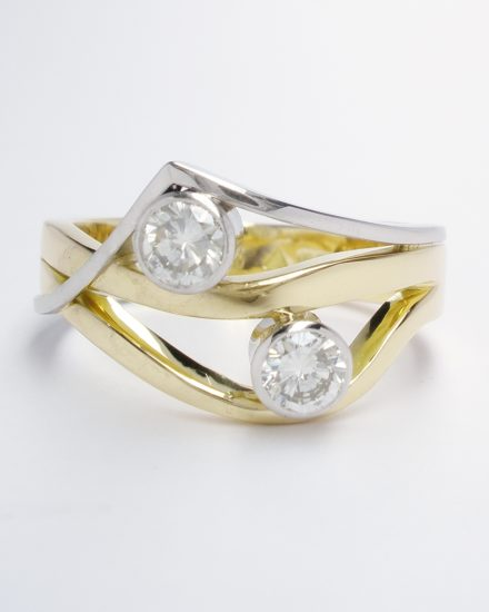 A 2 stone rub-over set round brilliant cut diamond wave & wishbone style ring mounted in 18ct. yellow gold and platinum.
