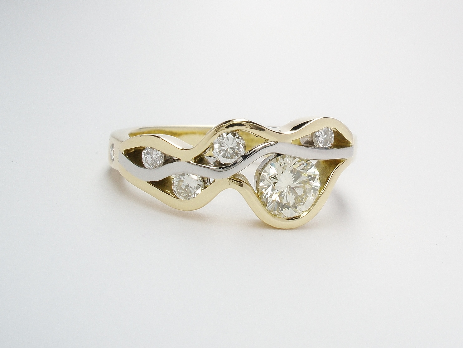 A 6 stone round brilliant cut diamond 'wave' style ring mounted in 18ct. yellow gold and platinum.
