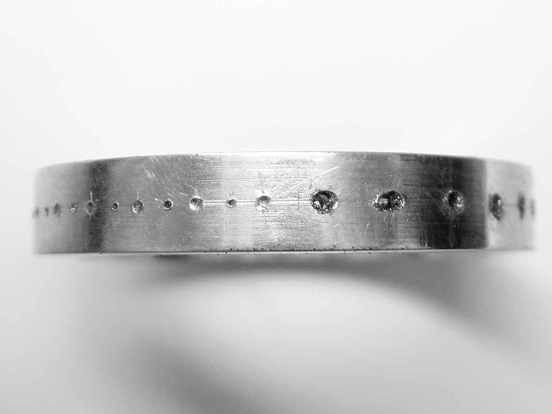The centre punch marks on the left - the 0.6mm pilot holes on the right