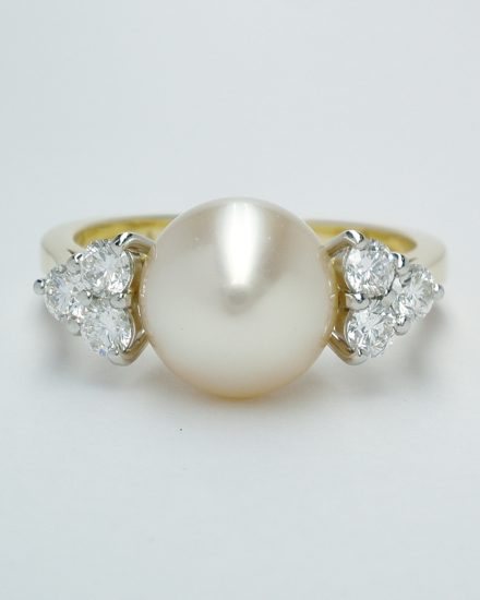 A 9mm South Sea pearl and round brilliant cut diamond 7 stone ring mounted in 18ct. yellow gold and platinum.
