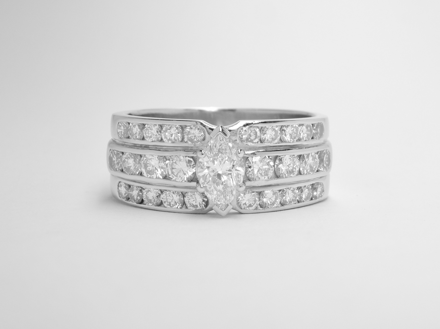 A triple banded channel set round brilliant cut diamond ring, mounted in palladium and platinum with a 0.41ct. 'D' colour, VS1 clarity marquise diamond claw set in the centre.