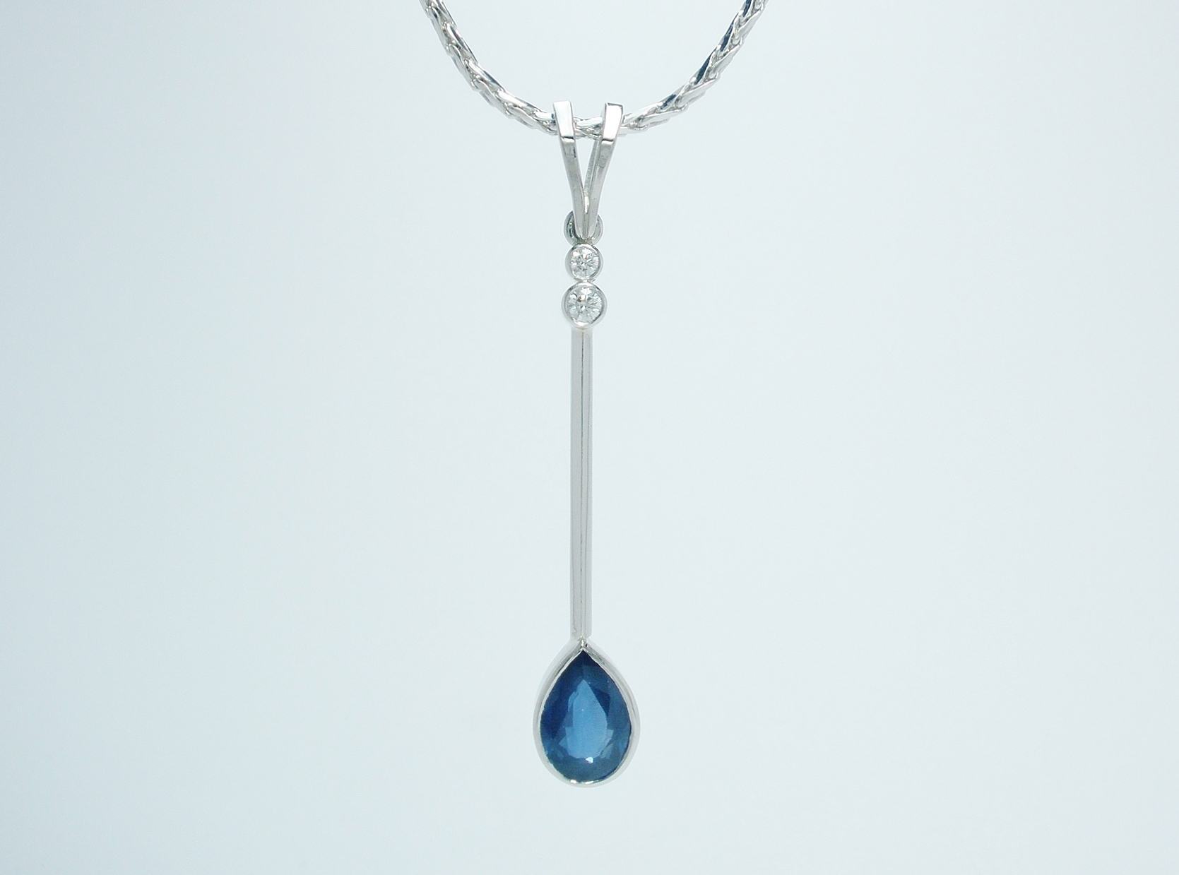 A 3 stone pear shaped sapphire and round brilliant cut pendulum style pendant mounted in palladium and platinum.