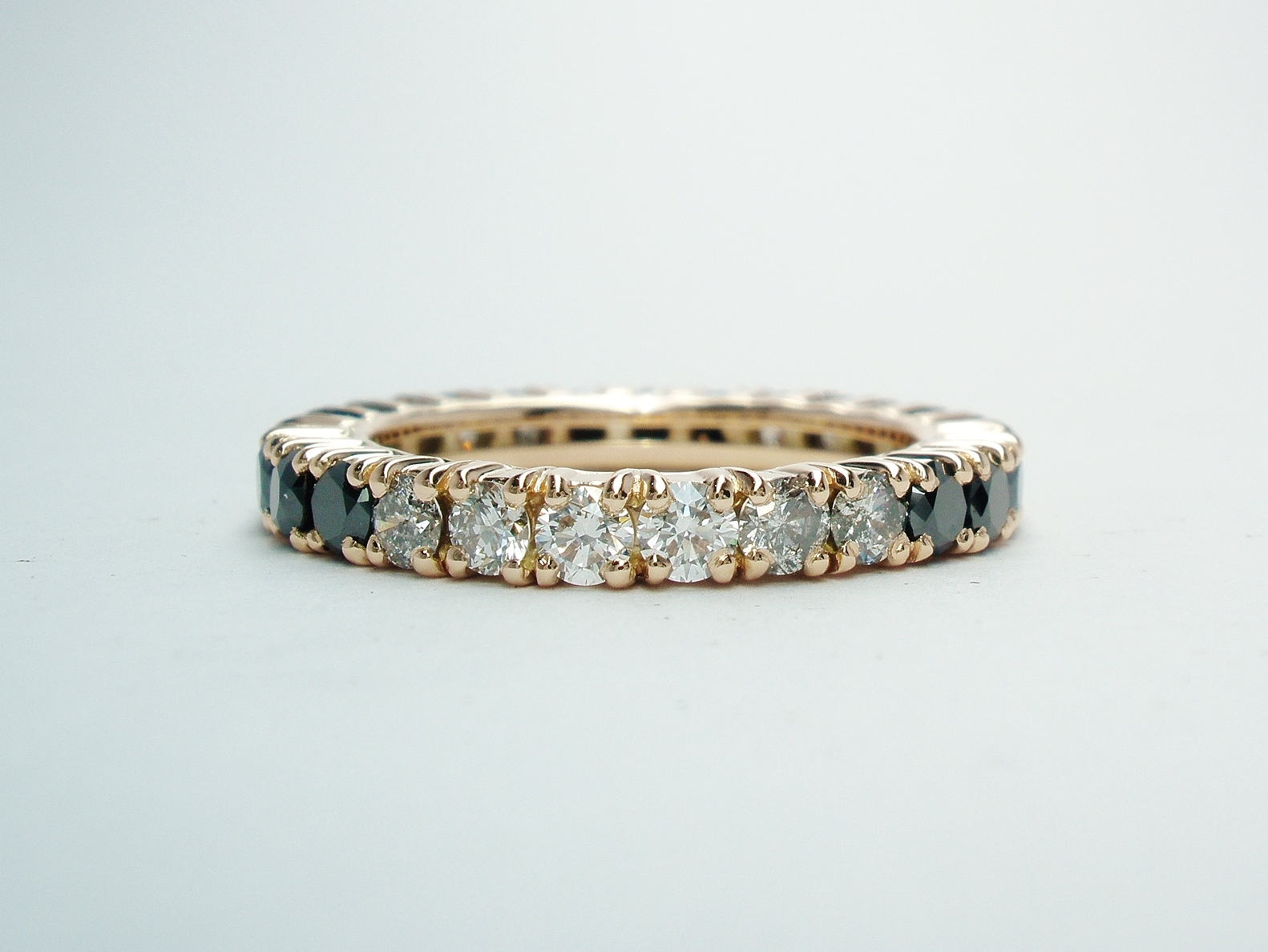 A black, 'grey' & white diamond full hoop diamond ring mounted in red gold.