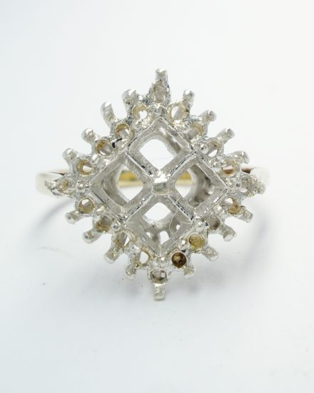 The original had 4 square cut emeralds in the centre with 20 round brilliant cut diamonds surrounding.