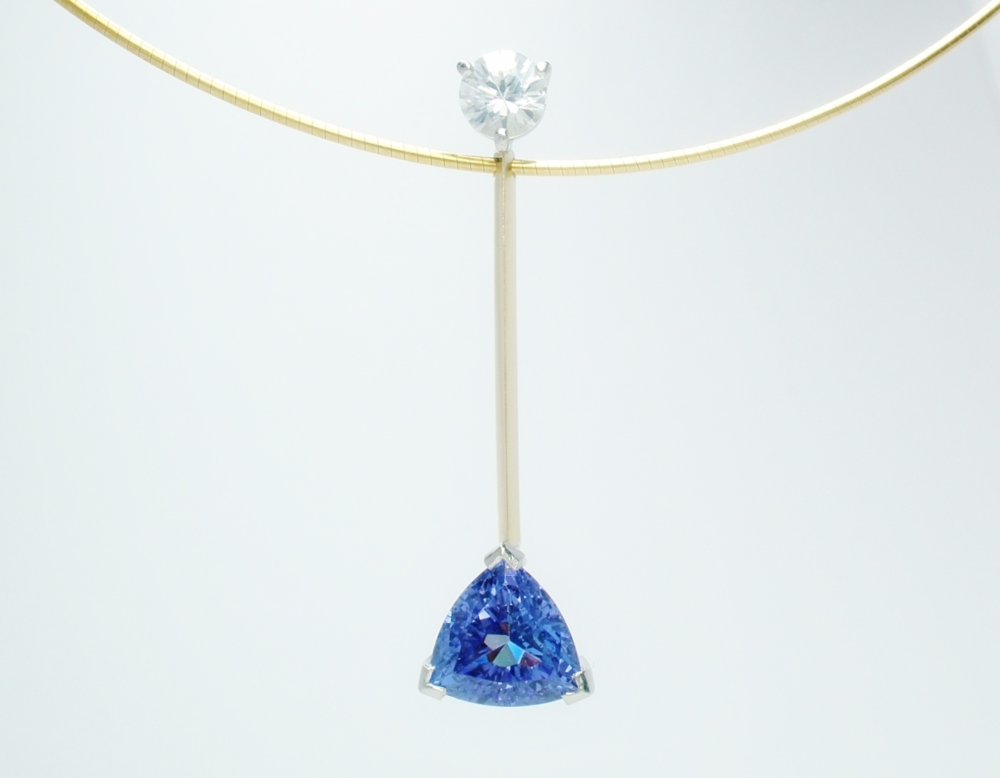 A 2 stone trilliant tanzanite and round brilliant cut diamond pendulum style pendant mounted in 18ct. yellow gold & platinum.