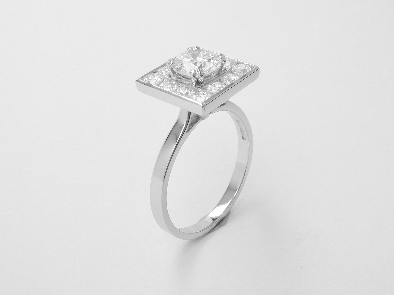 A 13 stone round brilliant cut diamond square channel set ring mounted in platinum.