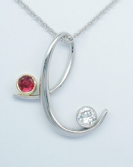 A ruby and diamond stylised 'e' platinum pendant.