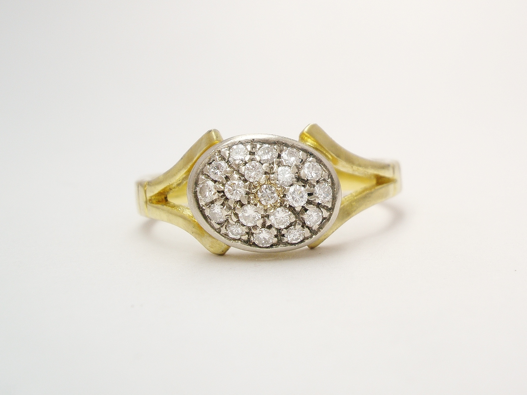 An 18ct. yellow gold & platinum topped pave` set diamond oval cluster.