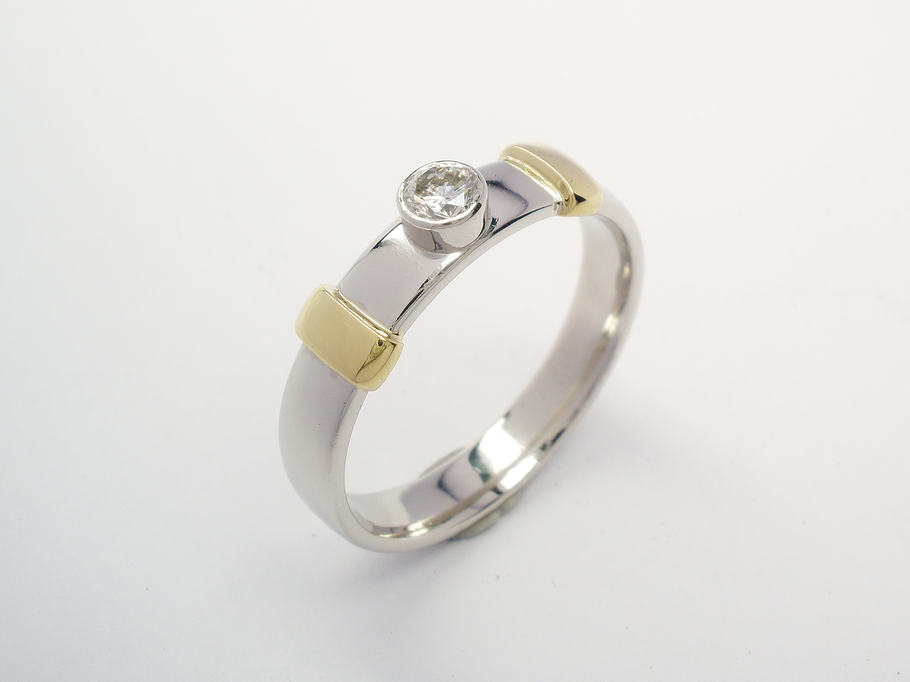 A platinum and 18ct yellow gold rub-over set single stone diamond dress ring.