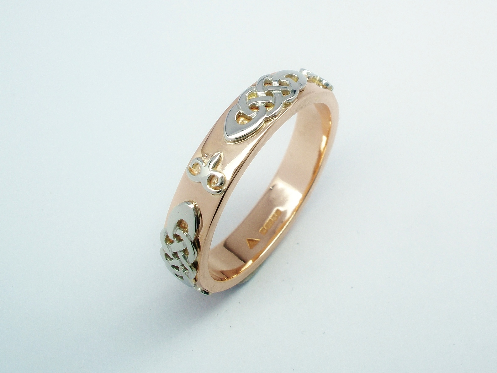 A red gold gent's wedding ring with platinum Celtic and Kazakh style motif overlays.
