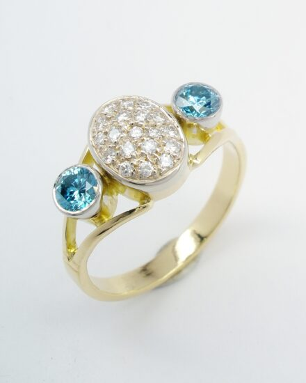 The oval cluster turned to go up the finger and flanked on either side with an HT-HP treated sky blue diamond rub over set in a platinum topped setting.