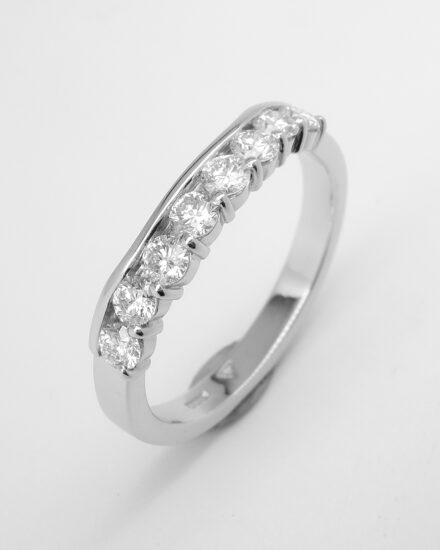 Platinum 8 stone part channel set diamond ring shaped to fit around a 3 stone diamond engagement ring.