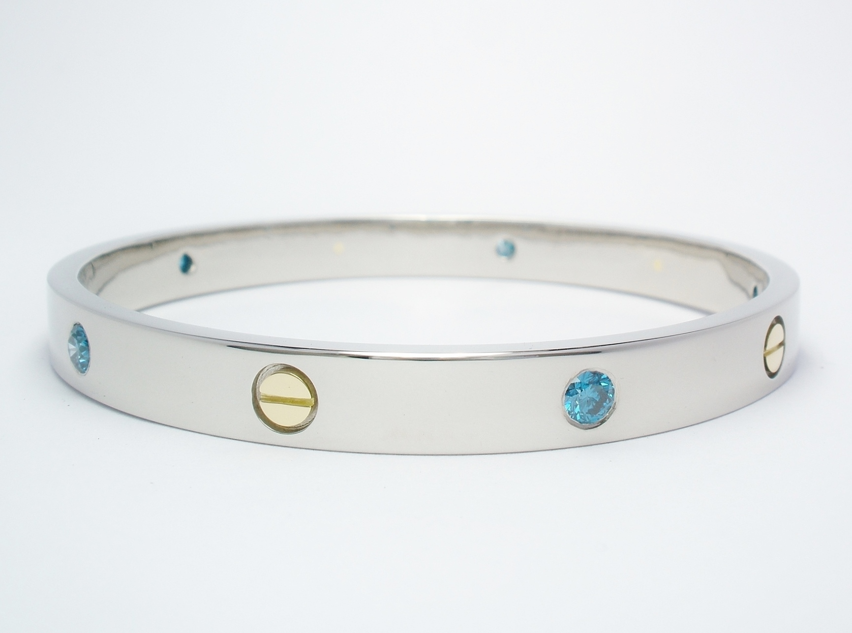 A solid palladium bangle with 18ct. yellow gold 'screw heads' inlayed and flush set with ocean blue round brilliant cut diamonds evenly spaced around and alternating with the screw heads.