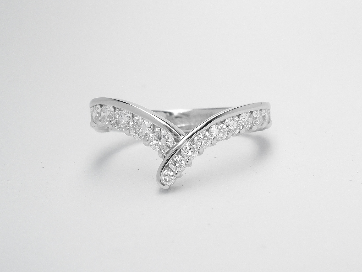 A 19 stone part channel set wishbone cross-over styled ring mounted in platinum. There are 12 tapering diamonds on the right side and 7 of the same size on the left side.