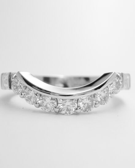 A 9 stone round brilliant cut and baguette cut diamond wedding ring mounted in platinum and shaped to fit around an oval emerald and half moon diamond ring.