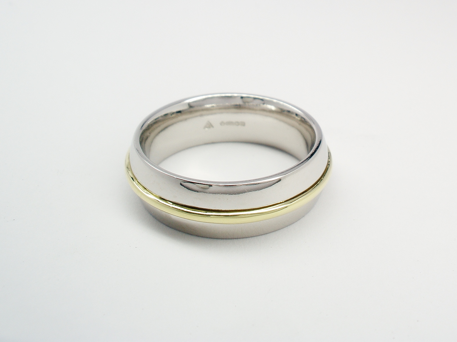 A platinum court sectioned wedding ring with an 18ct. Green gold wire inlayed in the centre.