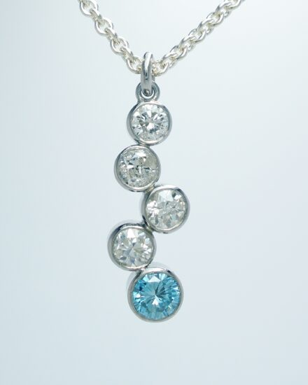 A 5 stone sky blue diamond and white diamond tumble pendant mounted in platinum.