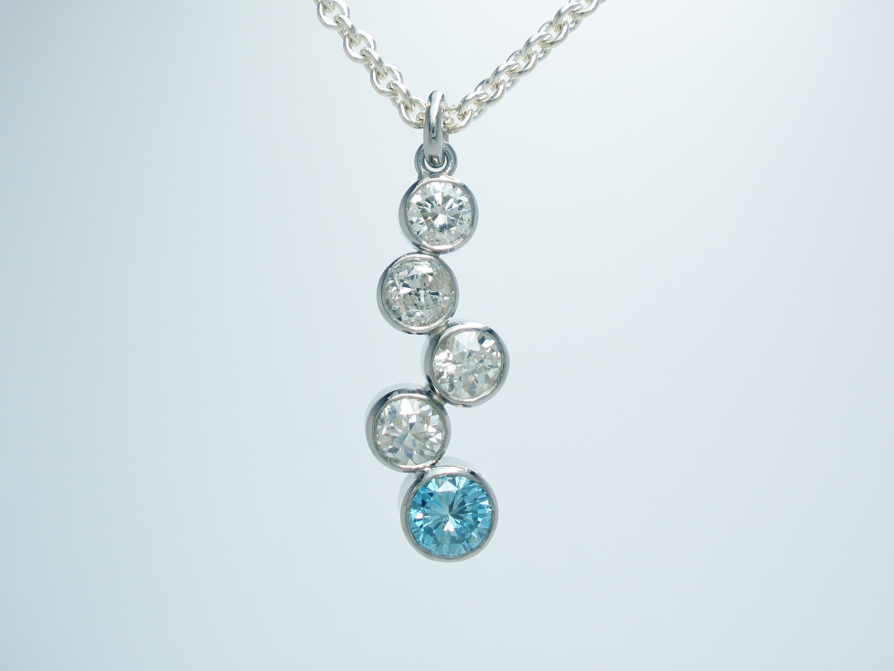 A 5 stone sky blue diamond and white diamond tumble pendant mounted in platinum.