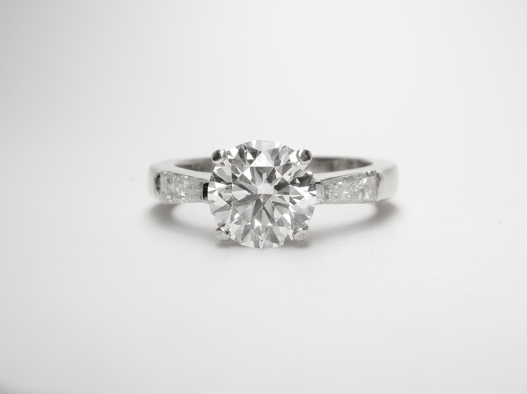 Before A single stone 1.50cts. round brilliant cut diamond ring with tapered baguette shoulders set in 18ct. white gold.